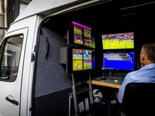 Ein fünfter Schiedsrichter sitzt in einem Übertragungswagen