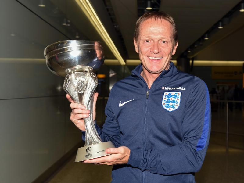Keith Downing, der Trainer von Englands U19-Fußball-Nationalmannschaft zeigt den Pokal auf dem Flughafen Heathrow in London