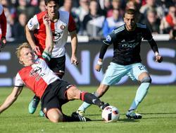Feyenoord-aanvoerder Dirk Kuyt speelt de bal weg voor de voeten van Ajacied Hakim Ziyech (r.). Op de achtergrond kijkt Eric Botteghin mee. (23-10-2016)