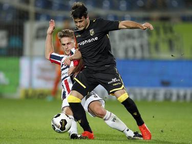 Valeri Qazaishvili (r.) vecht een stevig duel uit met Jordens Peters (l.) tijdens het competitieduel Willem II - Vitesse (06-08-2016).