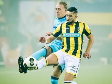 Rick Karsdorp (l.) en Adnane Tighadouini (r.) steken beiden een been uit om de bal te toucheren. (26-01-2017)