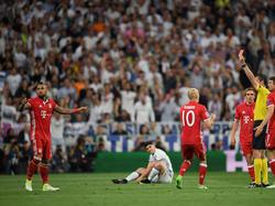 Arturo Vidal (l.) krijgt zijn tweede gele kaart van Viktor Kassai (r.). Arjen Robben (m.) snapt daar niets van. (18-04-2017)