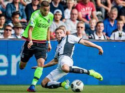 Hakim Ziyech (l.) snelt langs zijn directe tegenstander Robin Gosens (r.) van Heracles Almelo. (18-09-2016)
