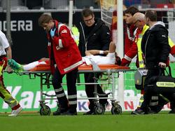 Der Düsseldorfer Kevin Akpoguma wird mit einer Trage vom Spielfeld geschoben