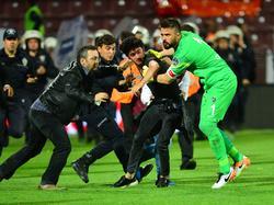 Trabzonspor-Keeper Kivrak (r.) hilft, einen Fan dingfest zu machen, der zuvor auf einen der Assistenten eingeprügelt hatte