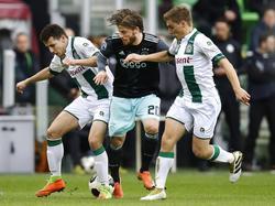 Lasse Schöne (m.) wordt door Oussama Idrissi (l.) en Ruben Jenssen (r.) op de huid gezeten tijdens FC Groningen - Ajax. (05-03-2017)