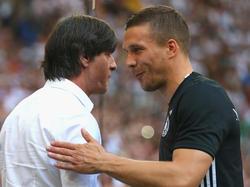 Lukas Podolski (r.) beim Handschlag mit Bundestrainer Joachim Löw