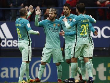 Lionel Messi (m.) is het middelpunt van de feestvreugde. De aanvaller scoort tweemaal tegen Osasuna. (10-12-2016)