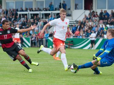 Chinedu Ekene (l.) schiet op doel, maar doelman Mike van de Meulenhof (r.) kan keren tijdens de oefeninterland tussen Duitsland u17 en Oranje u17. (13-09-2015)