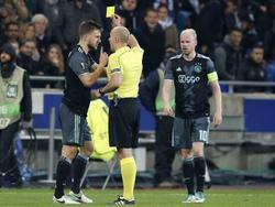 Szymon Marciniak (m.) toont Joël Veltman (l.) de gele kaart terwijl Davy Klaassen (r.) daar niet blij mee is. (11-05-2017)
