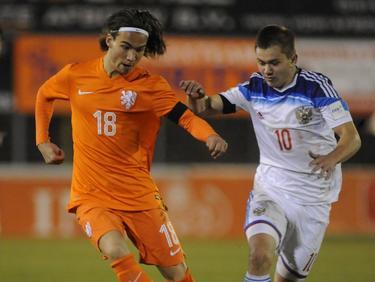Mink Peeters (l.) probeert als speler van Oranje U18 de Rus Ivan Obliakov (r.) van zich af te houden. (24-03-2016)
