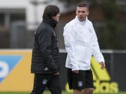 Lukas Podolski (r.) praat tijdens de training van de nationale ploeg van Duitsland met bondscoach Joachim Löw (l.) (21-03-2017).