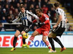 Dani Osvaldo (m.) in duel met Davide Santon (l.) en Mike Williamson (r.) tijdens Newcastle United - Southampon. (14-12-2013)