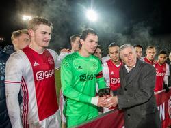 Niemand minder dan Sjaak Swart (r.) overhandigt aanvoerder Norbert Alblas (m.) de eerste bronzen stier voor Jong Ajax. De beloften pakten tegen FC Eindhoven (1-1) de eerste periodetitel in de clubgeschiedenis. (24-02-2017)