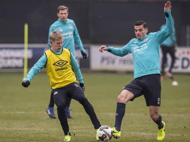 Menno Koch (r.) en Oleksandr Zinchenko (l.) komen tegelijkertijd bij de bal tijdens een training van PSV. (10-02-2017)